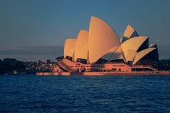 Opera House during sunset standing in Blue Ocean shore and sky line in Sydney on a summer day stock photography