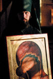 The icon painter. MONASTERY OPTINA PUSTYN, KOZELSK RUSSIA - MARCH 25, 2000:Icon painter holds in hands russian icon Royalty Free Stock Photo