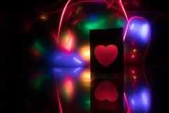 Icona al neon vaga del cuore su un fondo scuro Spazio della copia con cuore variopinto luminoso rosso su fondo nero immagine stock libera da diritti