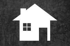 Icona bianca della casa sul fondo scuro del cemento come simbolo dell'ipoteca Fotografie Stock Libere da Diritti