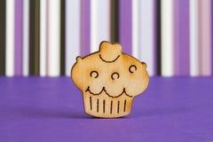 Icona di legno del dolce su fondo a strisce porpora Fotografie Stock Libere da Diritti