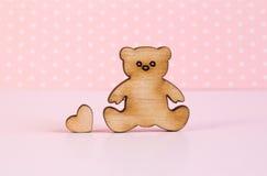 Icona di legno dell'orsacchiotto con poco cuore su fondo rosa Fotografie Stock