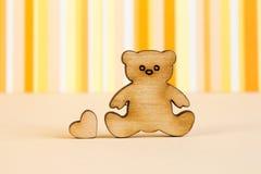 Icona di legno dell'orsacchiotto con poco cuore sulle sedere a strisce arancio Immagine Stock