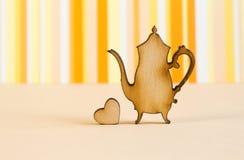 Icona di legno della teiera con poco cuore su backgr a strisce arancio Immagini Stock