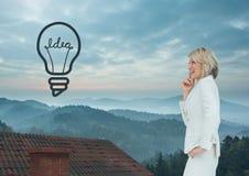 Icona e donna di affari della lampadina che stanno sul tetto con il camino ed il paesaggio nebbioso Fotografia Stock Libera da Diritti