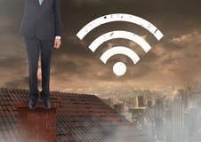 Icona ed uomo d'affari di Wi-Fi che stanno sul tetto con il camino e la città nuvolosa Fotografie Stock
