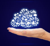 Icone del computer della tenuta della mano nella forma della nuvola su fondo blu Fotografia Stock Libera da Diritti