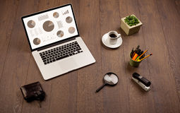 Icone del grafico del diagramma a torta sullo schermo del computer portatile con gli accessori dell'ufficio Fotografie Stock