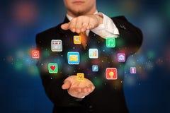 Icone dell'applicazione della tenuta dell'uomo d'affari Fotografia Stock