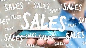 Icone di vendite della tenuta dell'uomo d'affari sopra la sua rappresentazione del telefono 3D Fotografia Stock