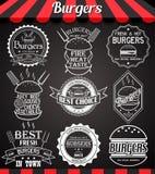 Icone, etichette, segni, simboli e distintivi stabiliti dell'hamburger di bianco sulla lavagna Immagine Stock