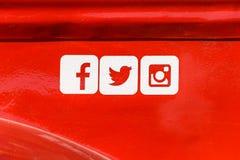 Icone sociali di media di Facebook, di Twitter e di Instagram sul fondo rosso del metallo Fotografia Stock