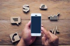 Icone tenute in mano di affari e del cellulare disposte sul pavimento di legno - concentrato Fotografie Stock Libere da Diritti