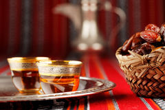 Iconic Abrian fabric tea and dates symbolise Arabian hospitality. Iconic Abrian fabric is graced with sybbols of Arabia, in particular Arabic tea and dates, they Stock Photos