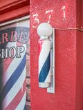 Iconic barber shop sign. Classic barber shop pole and sign, red building Royalty Free Stock Photo