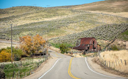 Iconic barn in Idaho with fall trees and country road Royalty Free Stock Images