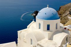 The iconic blue dome church on Santorini and the spectacular views over the Aegean ocean. The blue dome churches of Santorini sit majestically on the cliffs stock photos