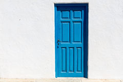 Free Iconic Blue Wooden Door Against Clear White Wall And Colorful Fl Royalty Free Stock Photography - 64586657