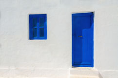 Iconic blue wooden door and window against clear white wall.  Royalty Free Stock Images