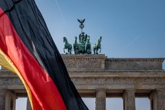 Berlin Brandenburg Gate with german flag royalty free stock photos