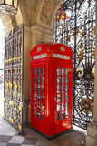 Iconic British red telephone box and beautiful metal gate lace Royalty Free Stock Images