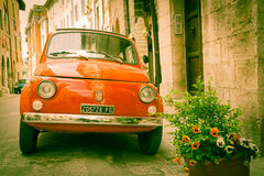 Iconic Italian car in grungy narrow street in small town. Royalty Free Stock Photo