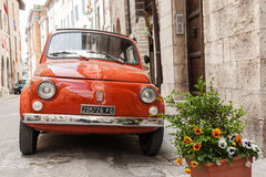 Iconic Italian orange Fiat car parked in traditional narrow stre Stock Photos
