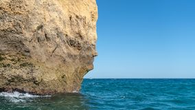 The iconic natural rock formation called The face in Praia da Marinha in Algarve, Portugal Royalty Free Stock Images