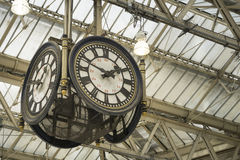 Iconic old clock Waterloo Station,London. Two of four faces of iconic historic clock hanging under the glass roof of Waterloo station, in London, England Royalty Free Stock Image