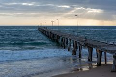 The iconic Port Noarlunga Jetty with sun rays above in South Australia on 12th September 2018 stock photography