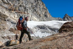 Iconic Portrait of Nepalese Mountain Guide staying and looking up. Iconic Portrait of Nepalese professional Mountain Guide staying on Rock and looking up at high Stock Photo