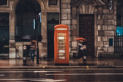 Iconic red British telephone booth. On a wet rainy pavement in front of city shops illuminated in the gloomy weather Stock Photo