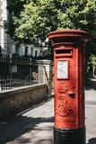 Iconic red postbox belonging to Royal Mail on a street in London stock photography