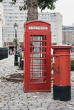 An iconic red telephone box next to a red post box in St Katharine Docks, London. Stock Photography