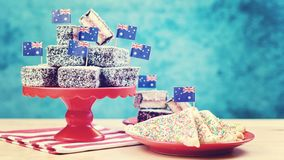 Iconic traditional Australian party food, Lamington cakes and Fairy Bread,. On a red, white and blue background., with applied vintage wash filter royalty free stock image