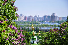 Iconic view to a monastery Vydubitsky and Dnieper River from a botanical garden of Kyiv with blooming lilac Stock Image