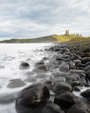 An iconic viewpoint of Dunstanburgh Castle, Northumberland. A classic view of the ruined tower of Dunstanburgh Castle, Northumberland, UK, from the famous black Stock Photo