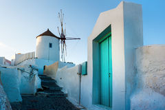Iconic Windmill in Oia, Santorini, Greece. The village of Oia, although devastated by the 1956 earthquake, still remains a dramatic and striking village at the Stock Photos