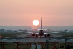 Iconical image of Airplane landing at an airport at sunset. Iconical image of Airplane landing at Seville airport at sunset Royalty Free Stock Images