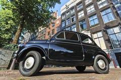 Iconisch Fiat 500 tegen oude met puntgevel huizen in Amsterdam Stock Afbeelding
