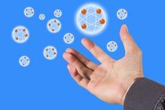 Icono de la red del átomo sobre la mano Fotos de archivo libres de regalías
