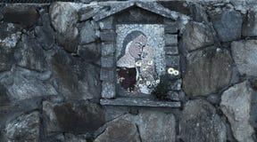 Icono de la Virgen María y del niño hechos de piedra en la cerca de la casa Fotos de archivo libres de regalías