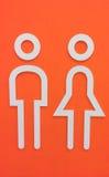 Icono de madera blanco del lavabo del hombre y de la mujer en fondo anaranjado de la pared Fotografía de archivo