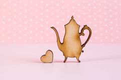 Icono de madera de la tetera con poco corazón en fondo rosado Fotografía de archivo libre de regalías