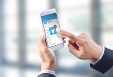 Icono del gorjeo del tacto de la mano del hombre de negocios en la pantalla móvil Fotos de archivo