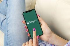 Icono del uso de Bing en el primer de la pantalla del iPhone X de Apple en manos de la mujer Icono del app de los anuncios de Bin imágenes de archivo libres de regalías