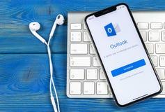 Icono del uso de la oficina de Microsoft Outlook en el primer de la pantalla del iPhone X de Apple Icono del app del Microsoft Ou imagen de archivo