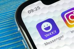Icono del uso del mensajero de Yahoo en el primer de la pantalla del smartphone del iPhone X de Apple Icono del app del mensajero Imagen de archivo libre de regalías