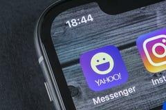 Icono del uso del mensajero de Yahoo en el primer de la pantalla del smartphone del iPhone X de Apple Icono del app del mensajero Imágenes de archivo libres de regalías