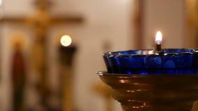 Icono-lámpara azul con la vela ardiendo en el chirch ortodoxo